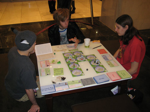 A group plays Collateral Damage: The Anime Board Game in the hotel lobby Saturday night